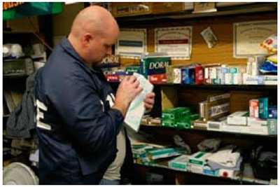 Graphic 16: A Law Enforcement Officer Checks for Cigarette Tax Stamps at a Retail Store - click to enlarge